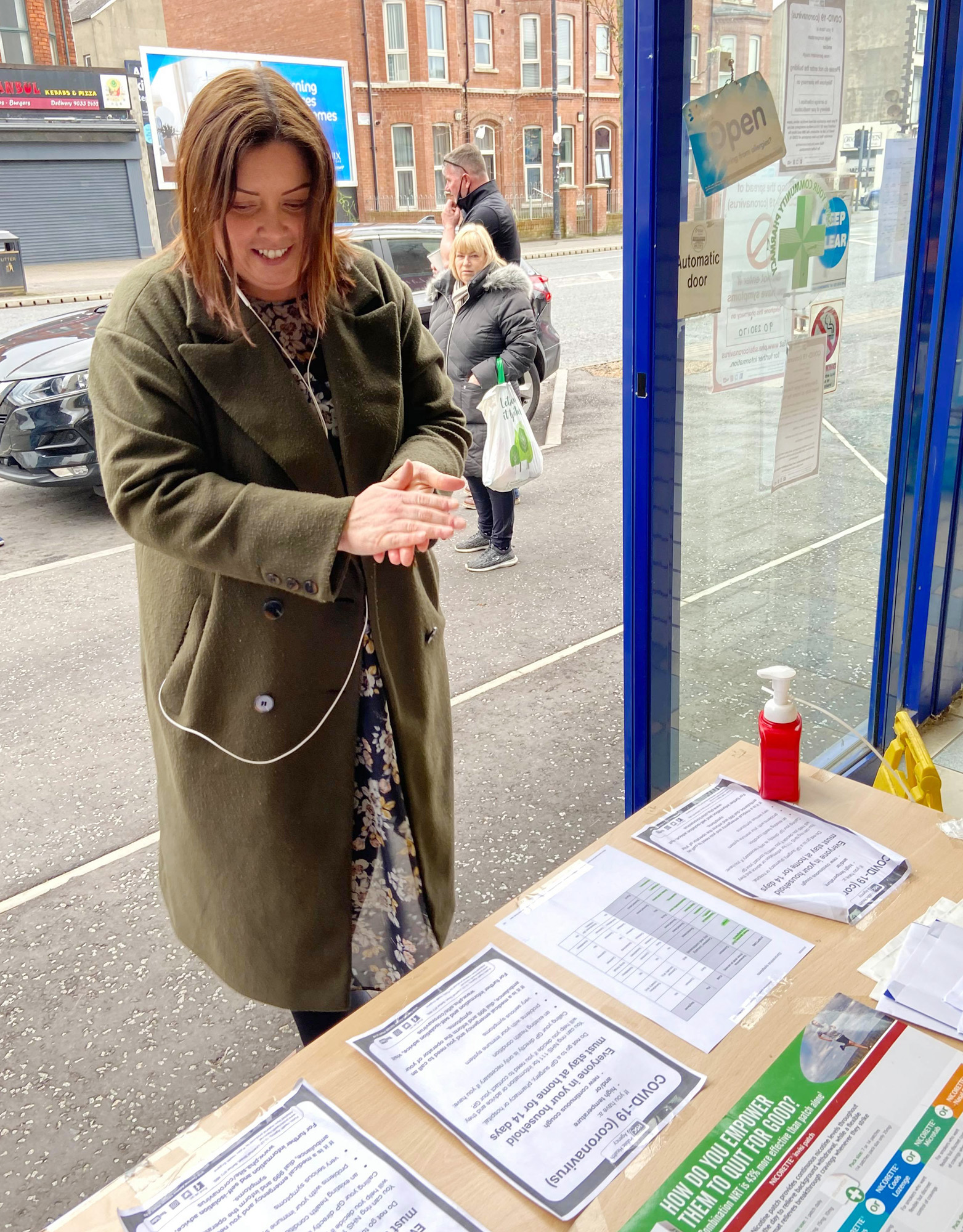 Communities Minister Deirdre Hargey uses sanitiser provided to customers at Medicare Pharmacy on Lisburn Road before entering the chemists.